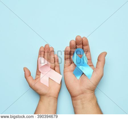 Female Hand Holding Pink Ribbon Bow, Male Hand Holding Blue Ribbon. Breast Cancer Awareness Campaign
