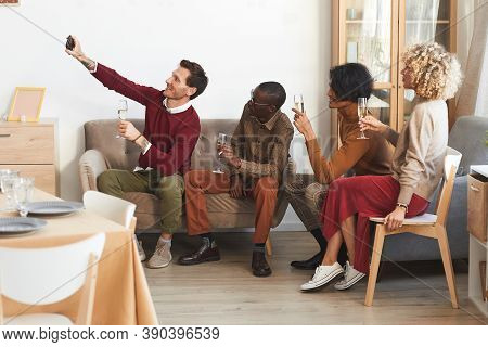Side View At Multi-ethnic Group Of Modern Adult People Taking Selfie With Champagne Glasses Indoors