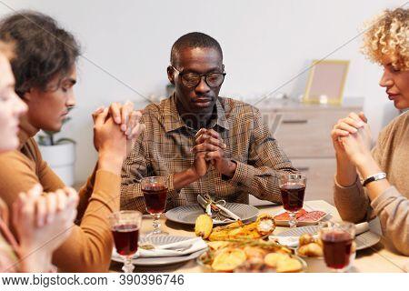 Multi-ethnic Group Of Modern Adult People Praying With Eyes Closed While Enjoying Thanksgiving Dinne