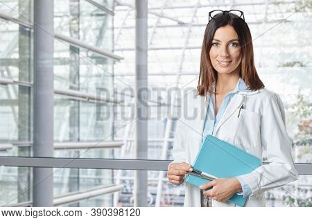 Smiling young female doctor in hospital, looking at camera standing with crossed arms.