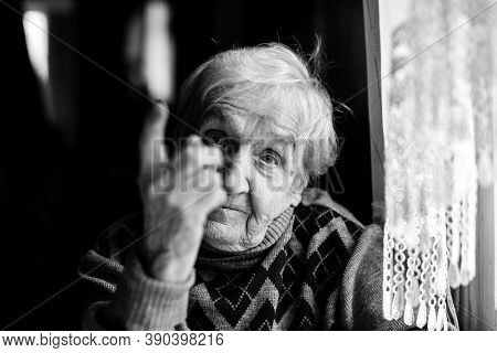 An elderly woman threatens with a finger looking at the camera. Black and white photography.