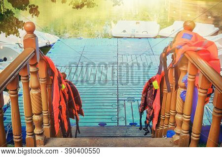 Entrance To The Boat Station In The Summer Park. Life Jackets On The Railing Of The Pier With Catama