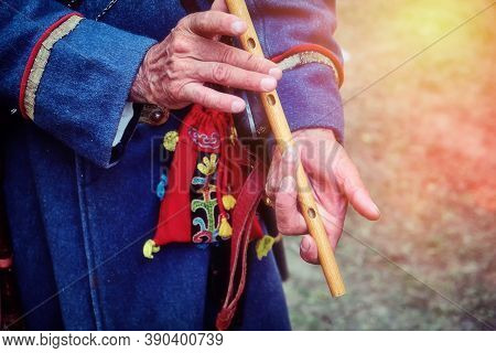 Nomad In Traditional Clothes Playing The Flute. Hands Of An Old Man With A National Pipe. A Musician