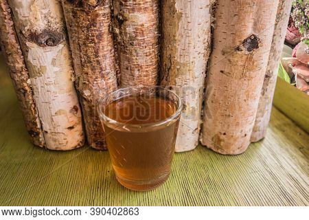Glass Of Homemade Ginger Tincture Or Ale On A Wooden Background.  A Stack Of Brown Drinks Against A