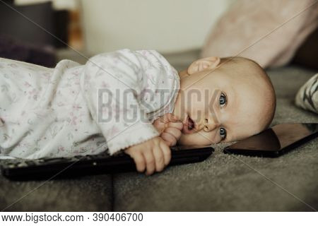A Child With A Remote Control And A Telephone, Addiction To Technology At A Young Age