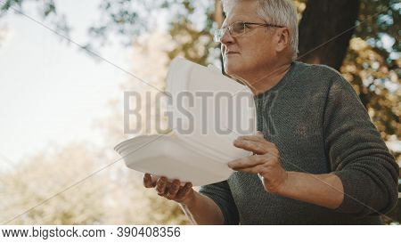 Old Vulnerable Homeless Man Getting Free Charity Meal. High Quality Photo