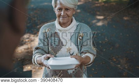 Old Vulnerable Homeless Woman Getting Free Charity Meal. High Quality Photo