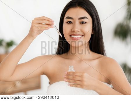 Happy Asian Woman Showing Hydrating Facial Serum. Bottle With Hydrating Face Serum In Young Lady Han