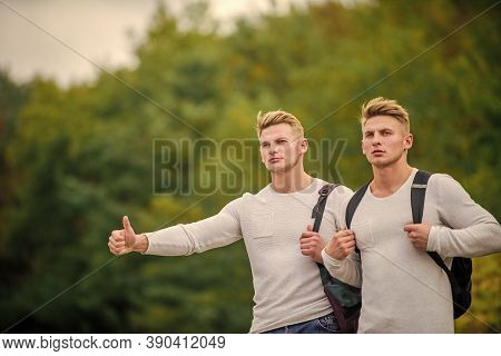Begin Great Adventure In Your Life With Hitchhiking. Company Friends Travelers Hitchhiking At Road N