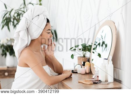 Side View Of Smiling Asian Woman Wrapped In Towel Looking At Mirror, Touching Her Silky Skin After S
