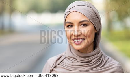 Modern Muslim Young Woman In Hijab Smiling Looking At Camera Standing Posing In Park Outdoors. Portr