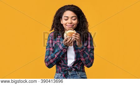 Delicious Meal. Portrait Of Hungry Black Female Model Eating Burger. Smiling African American Woman