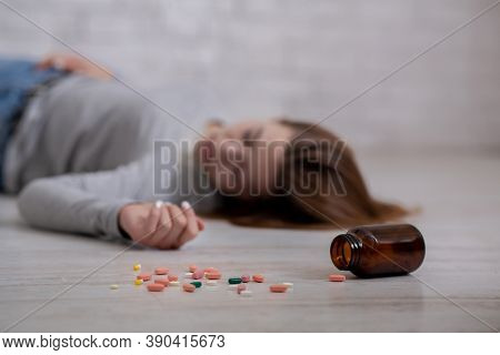 Young Woman Lying On Floor With Bottle Of Tablets Scattered On Floor, Committing Suicide, Selective