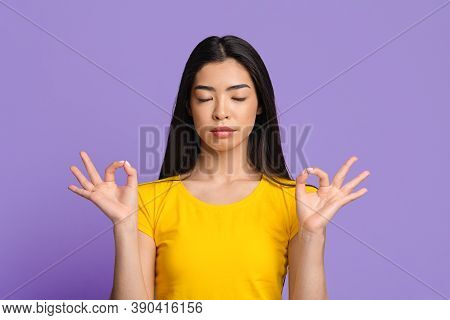 Zen. Relaxed Asian Woman Meditating Over Purple Studio Background, Staying Calm, Young Korean Female