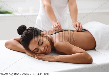 Relaxed African American Woman Having Hot Stone Massage At Modern Spa, Side View. Female Massage The