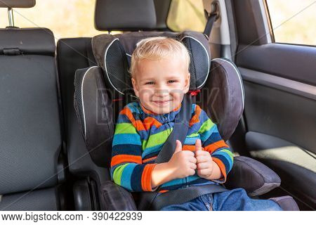 Little Baby Boy Sitting On A Car Seat Buckled Up In The Car.