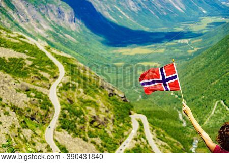 Tourist Woman With Norwegian Flag On Trollstigen Viewpoint. Trolls Path Mountain Road In Norway. Nat