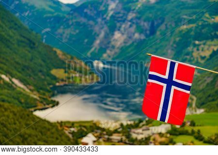Norwegian Flag And View Over Geirangerfjord From Flydalsjuvet Viewing Point. Tourist Attraction. Tou