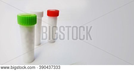 White Homeopathic Pills In Small Bottles Isolated In White Background