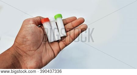 Homeopathic Pills In Small Bottles Hold In Hands In White Background