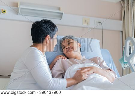 Happy Lover Woman Visits Best Friends Holding Hand For Recovering Sick Lying In Hospital, Looking Wi