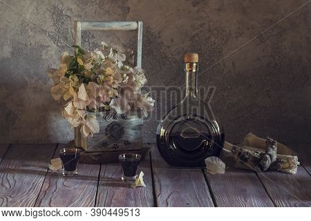 Still Life With Homemade Liquor In A Bottle And Stacks And A Wooden Basket With Flowers On A Wooden