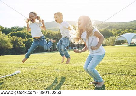 Children Play Tug Of War In The Park. A Group Of Cute Children Playing Actively Together In Nature.