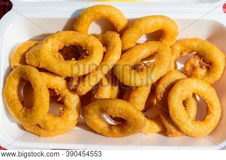 Large Group Of Freshly Fried Calamari And Onion Rings On Display For Sale At A Street Food Festival,