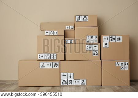 Cardboard Boxes With Different Packaging Symbols On Floor Near Beige Wall. Parcel Delivery