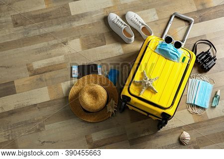 Flat Lay Composition With Suitcase, Protective Masks, Antiseptic Spray And Personal Items On Wooden
