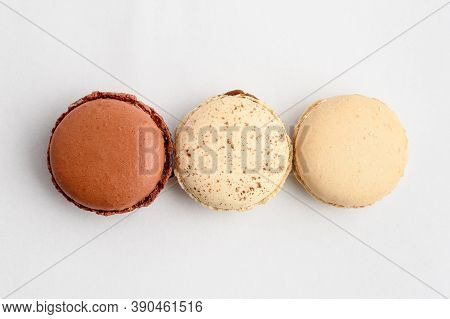 Top View Of Three Sweet Vivid Brown Chocolate, White Vanilla And Coconut French Macaron Isolated On