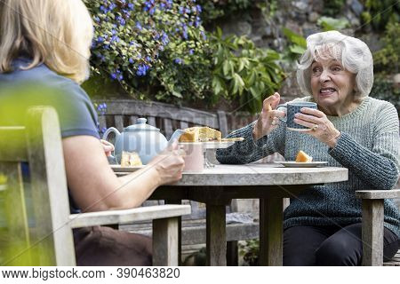 Mature Woman Visiting Lonely Senior Mother In Garden During Lockdown