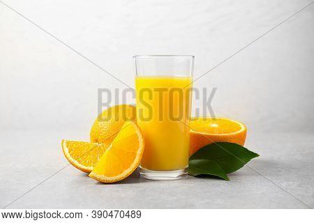 Tasty Orange Juice, Fresh Fruits And Green Leaves On Light Table