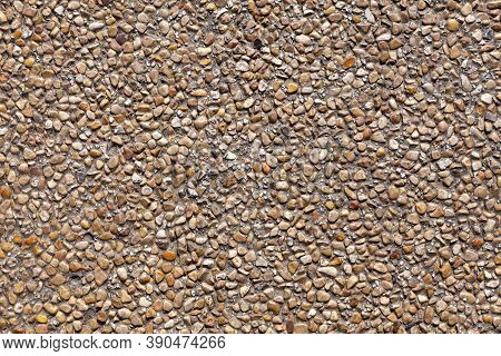 The Wall Is Decorated With Small Natural Pebbles Of Brown Color. Background Image, Texture