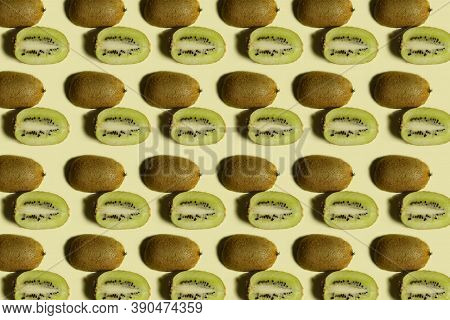 Kiwi Pattern. Repetition Of Kiwi Halves On A Yellow Background. Colorful Food Background. Fruit Patt