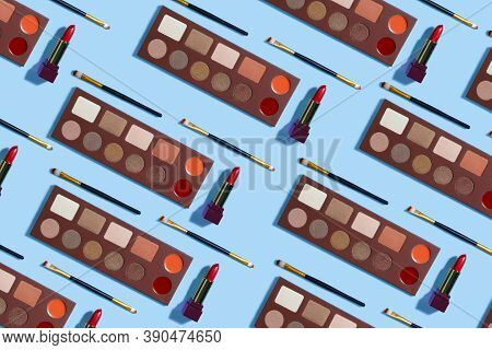 Cosmetics Patern.repeat Set Of Eye Shadows, Brushes And Lipstick On A Blue Background. Makeup Backgr