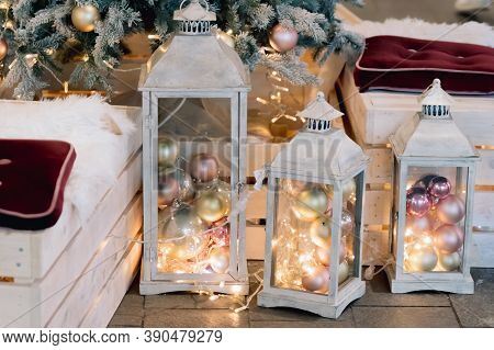 Lantern With Holiday Baubles On Decorated Christmas Tree Background In Living Room Interior. Winter