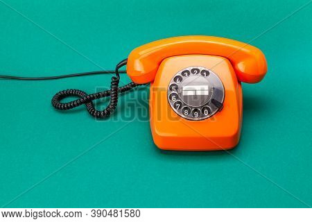 Retro Phone Orange Color, Vintage Handset Receiver On Green Background.