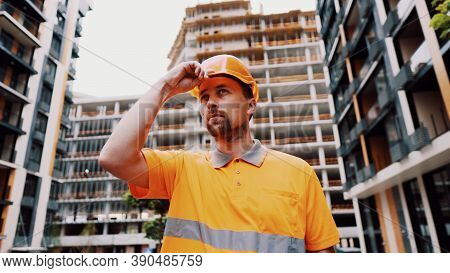 Construction Worker Putting On His Safety Gear Helmet At Job Site. Safety First, Profession Concept.