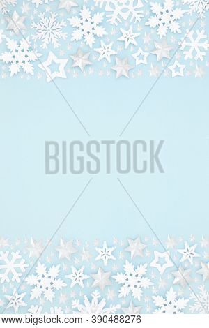 Star & snowflake Christmas background border composition on pastel blue. Winter, Xmas & New Year festive scene for the holiday season. Flat lay, top view, copy space.
