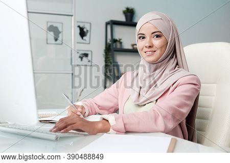 Happy young pretty Muslim woman in hijab and smart casualwear looking at you while sitting by table in front of computer monitor in office