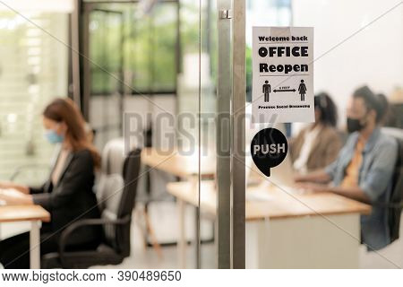 Signage of Office Reopen with social distancing practice with blurred background of Asian team business people working and wear face mask in new normal office to prevent covid-19 virus spreading.