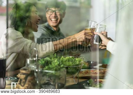 Happy asian multigenerational family of dad mom daughter girl and grandfather cheers together during lunch meal together with joyful. Happy family engagement togetherness concept. Taken outside window