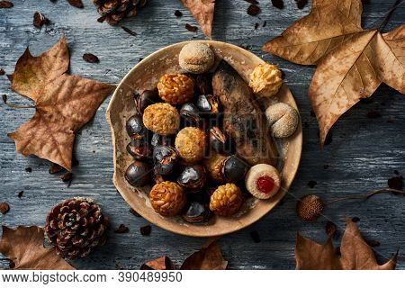 high angle view of a plate with some roasted sweet potato, some roasted chestnuts and some panellets, typical confection of Catalonia, Spain, eaten traditionally in All Saints Day, on a rustic table