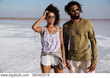 Loving young african couple walking along the seashore, holding hands