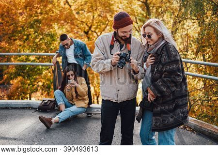 Dressed In Seasonal Clothing Group Of Four Friends Photographing And Getting Fun On Weekends In Autu