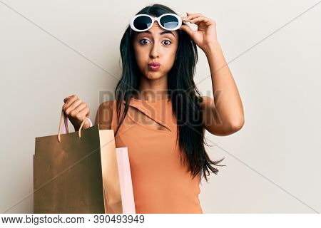 Beautiful hispanic woman holding shopping bags wearing sunglasses puffing cheeks with funny face. mouth inflated with air, catching air.