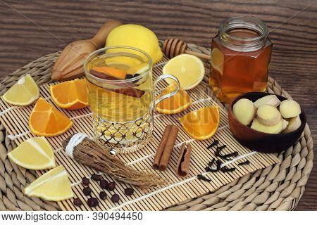 Alternative herbal remedy for cold & flu remedy with hot drink in a glass with fresh ginseng, cloves, ginger, lemon, orange, honey, cinnamon & hawthorn berries. Immune boost healthcare concept.