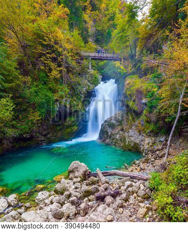 Picturesque old bridge over the Vintgar mountain gorge. Powerful rumbling waterfall on a mountain river. Slovenia. The concept of active and photo tourism