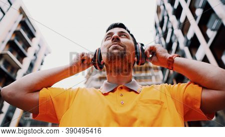 Man Wearing Safety Equipment Hearing Protection. Worker Wearing Noise Cancelling Ear Defenders Or Ea